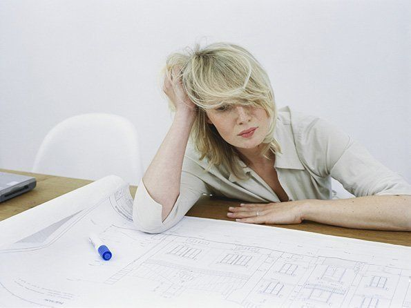 Overworked Woman with Architectural Plan